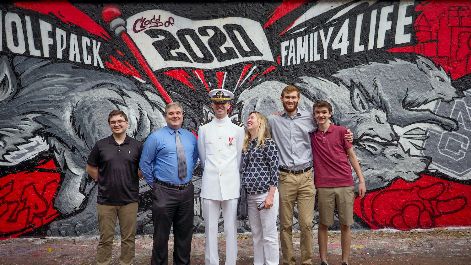 A Naval ROTC student celebrates graduation surrounded by his family in front a mural by the free expression tunnel. Photo by Marc Hall
